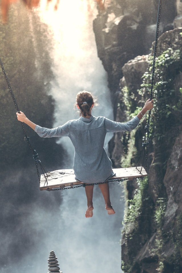 女性が崖でブランコに乗っている